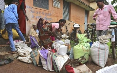 A woman ties a sack of subsidised food outside a ration shop in Seoni village, Chhattisgarh